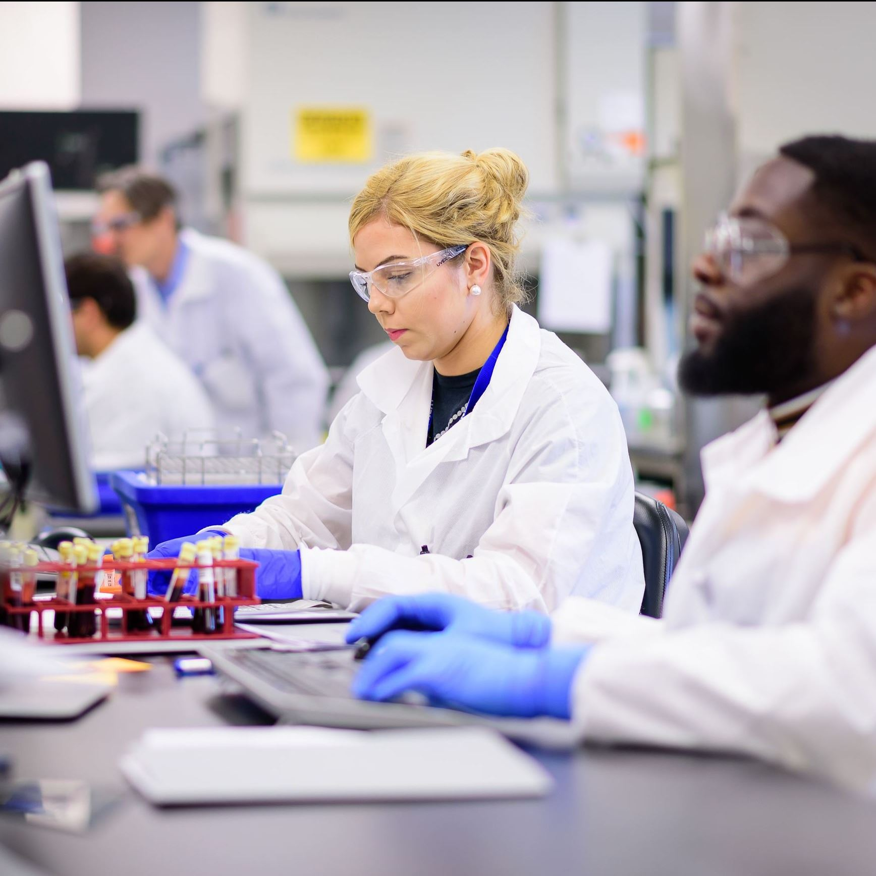 Men and women wearing white coats and protective eyewear in a lab